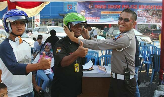 Petugas Beri Helm Gratis Kepada Pengandara Roda Dua